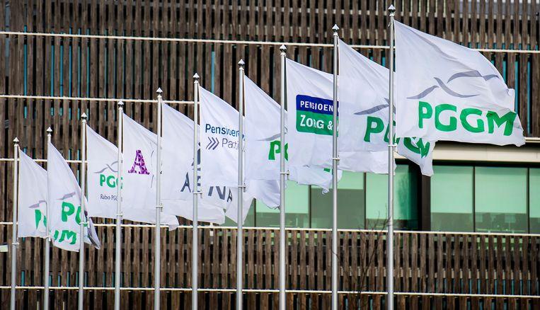 Vlaggen van diverse pensioenfondsen wapperen voor het hoofdkantoor van pensioenbelegger PGGM in Zeist. Beeld ANP