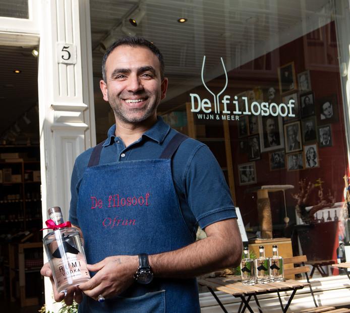 Ofran Badakhshani met een fles vodka van het merk Rumi voor zijn winkel De Filosoof in de Papestraat.