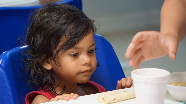 Een meisje krijgt een kopje soep van een vrijwilliger in een migratiecentrum in McAllen in Texas.