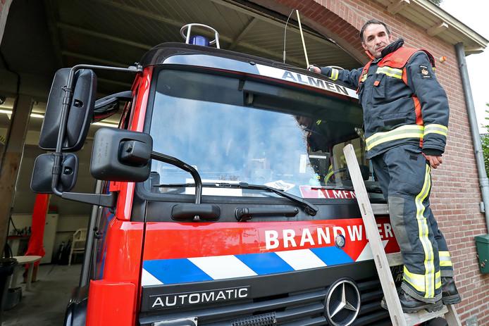 Postcommandant Freddy Heuvelink op een oude ladder ,voor een oude karzerne en oude brandweerwagen