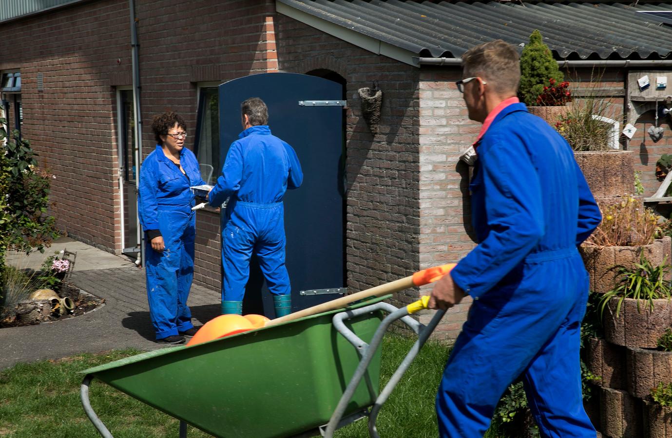 Henk Kuijpers achter de kruiwagen. Op de achtergrond Pim en Horry, die de staldeur aan het schilderen zijn.
