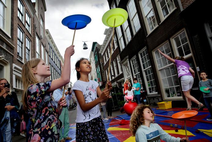 Kinderen vermaken zich tijdens de Buitenspeeldag met circusacts op de Voorstraat in Dordrecht