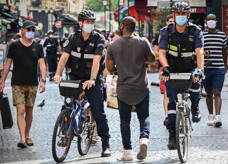 Parijse politieagenten vragen mensen hun mondmaskers op te zetten. Beeld AFP