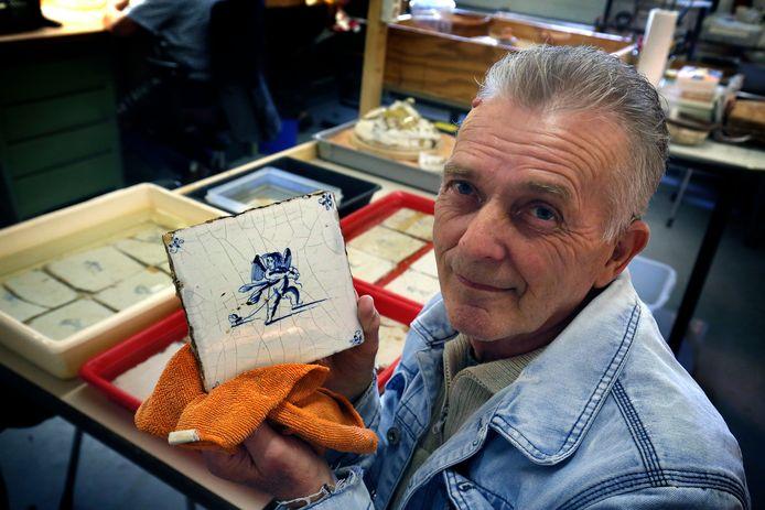 Ton Wijkamp, een van de vrijwilligers van het Archeologisch Depot van de gemeente Gorinchem, toont een tegeltje met een engeltje. De bijzondere vondst is dit weekeind te bekijken.