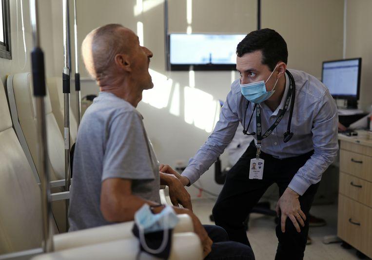 Een vrijwilliger in Brazilië krijgt het experimentele vaccin toegediend. Beeld REUTERS