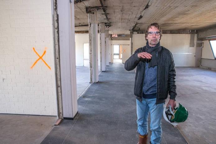 Projectleider Frank Docter bij een muur (met kruis) waar asbest in gevonden is.
