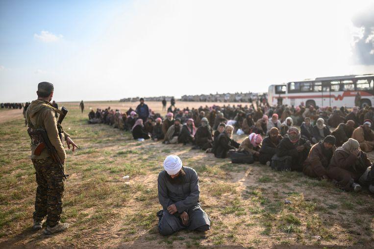 Leden van de Syrische Democratische Strijdkrachten houden in februari een groep mannen aan die zij aanzien voor IS-strijders. Beeld Bulent Kilic / AFP