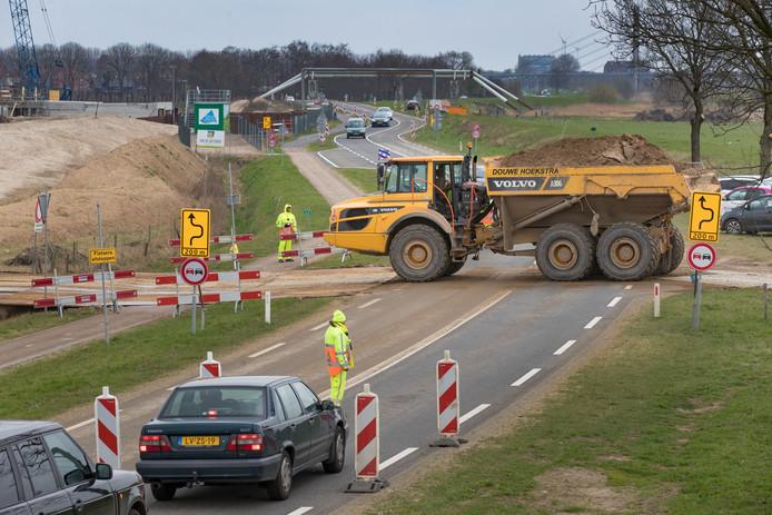 In de buurt van bouwput Reevediep rijden om de 3-4 minuten trucks en dumpers met zand over de Kamperstraatweg vanuit de uiterwaarden die het zand naar de dijken brengen.