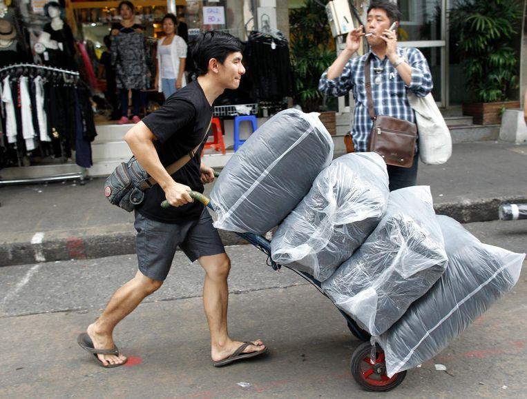 Een winkelier brengt zwarte kleding naar de markt. Beeld Afp