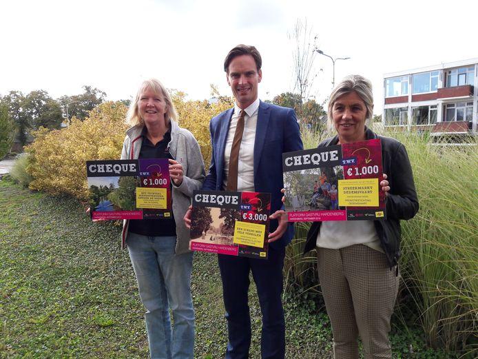 Immy van Huizen van De Koppel, wethouder Alwin te Rietstap en Gea van Dijk van Promotie Stichting Dedemsvaart (rechts) met de cheques van Platform Gastvrij Hardenberg.
