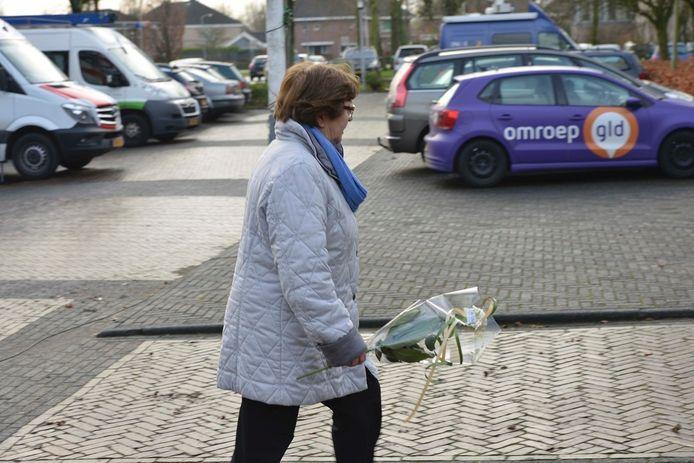 Een vrouw brengt bloemen als steun aan de raadsleden en het college, de dag na de rellen in Geldermalsen.