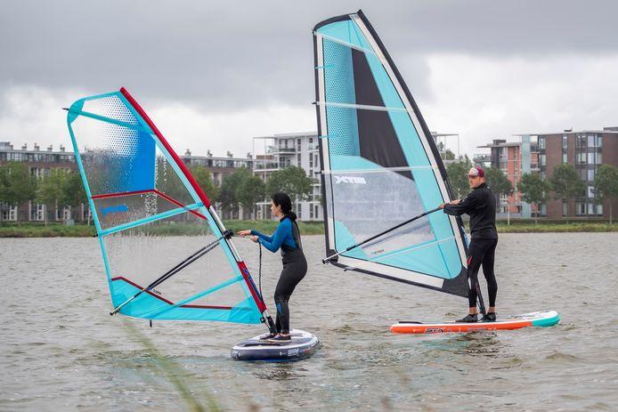 Roel Tieges (rechts) is zijn eigen surfschool begonnen. Hij geeft lessen op de Binnenschelde, zoals hier aan verslaggeefster Majda Ouhajji.