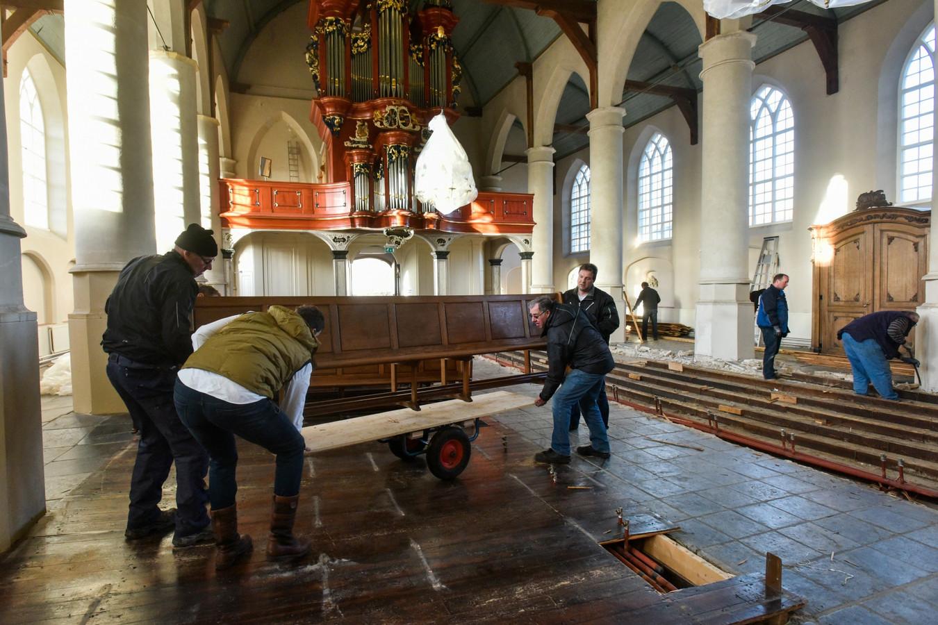 vrijwilligers halen banken weg uit jet kerkgebouw van de hervormde gemeente waspik