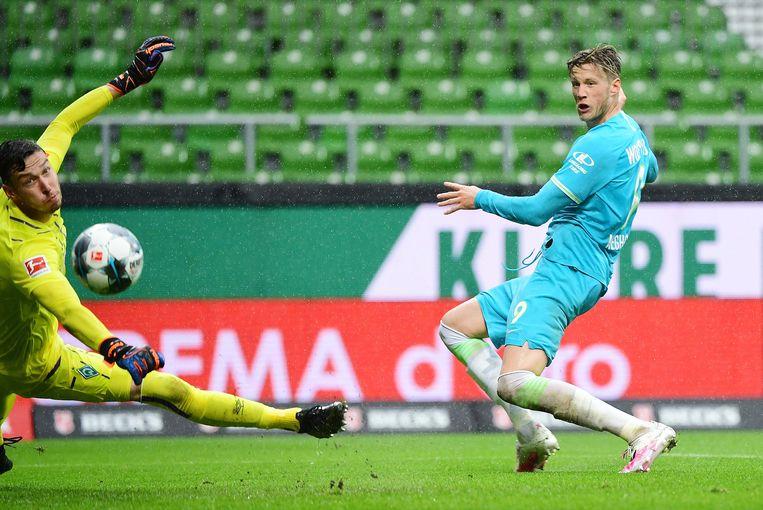 De Nederlandse aanvaller Wout Weghorst passeert Werder-doelman Jiri Pavlenka, waardoor Wolfsburg de wedstrijd met 0-1 wint. In de Bundesliga is vijftig procent van de wedstrijden in lege stadions tot dusver gewonnen door de uitploeg.  Beeld BSR Agency