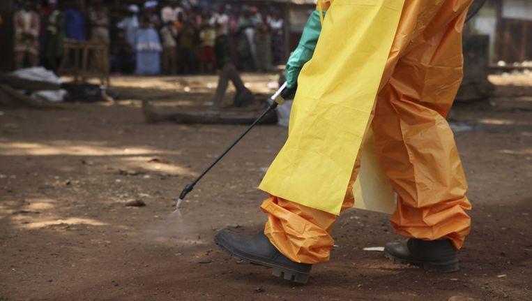 Een gezondheidswerker desinfecteert de grond rond een ebola-patiënt in Guinee Beeld reuters