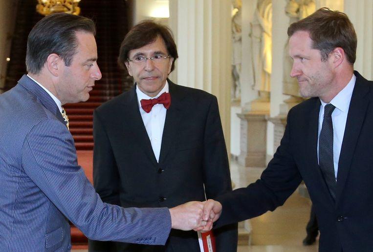 Bart De Wever (links) schudt Paul Magnette de hand, Elio Di Rupo kijkt toe.