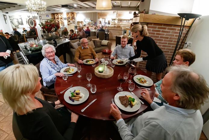 Evy Martens aan tafel bij haar gasten in restaurant De Haard.