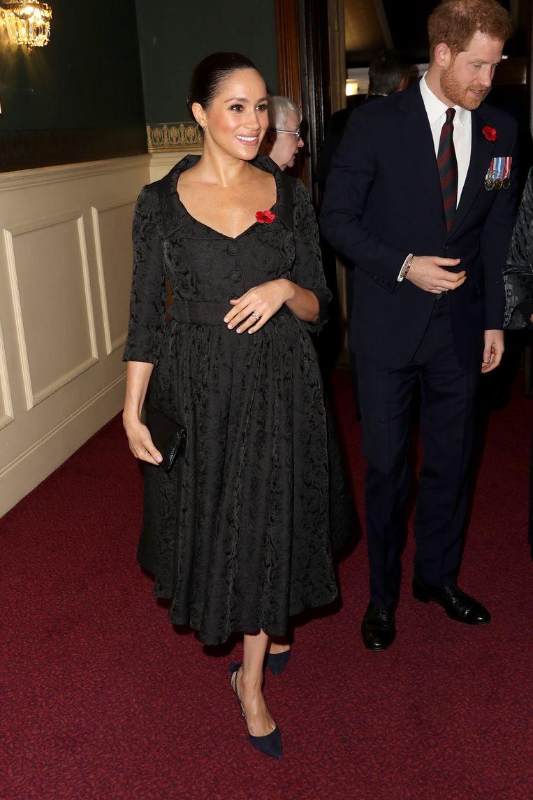 Meghan in loszittende jurk en met hand op haar buik - een beweging die Harry onbewust nadoet