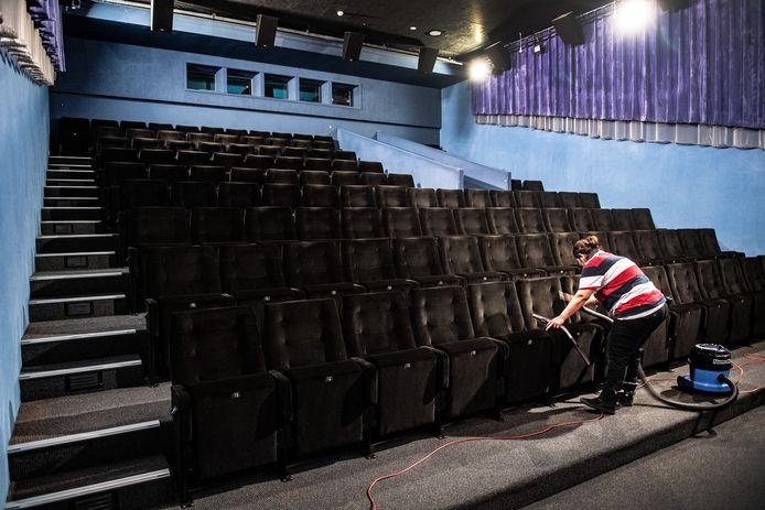 Een schoonmaker aan het werk in een lege filmzaal van LUX.