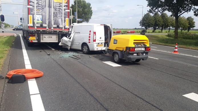 De bestelbus schoof onder de vrachtwagen.