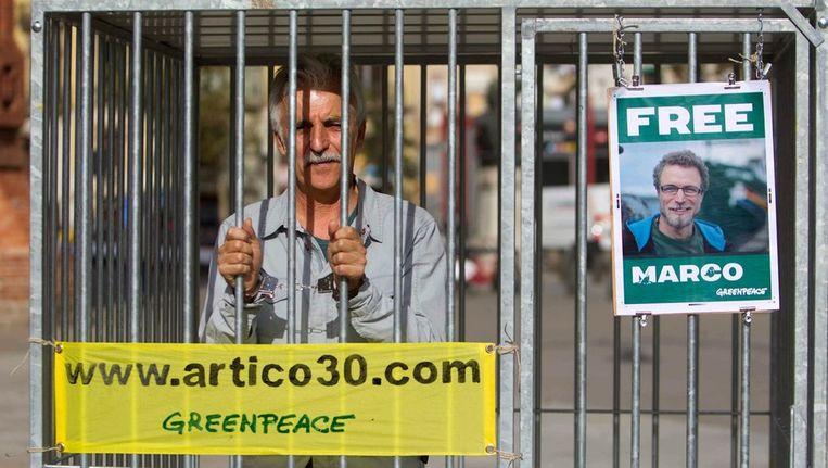 Een spanjaard protesteert tegen de arrestatie van de 30 activisten van Greenpeace. Beeld epa