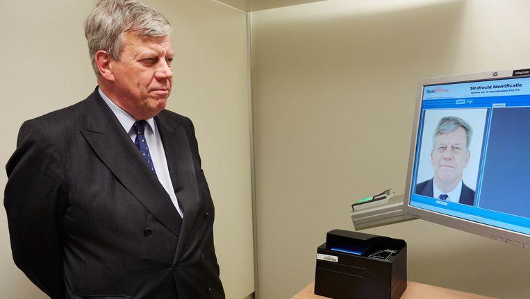 Minister Ivo Opstelten laat zijn identiteit controleren tijdens een werkbezoek aan een politiebureau in 2013. Beeld anp