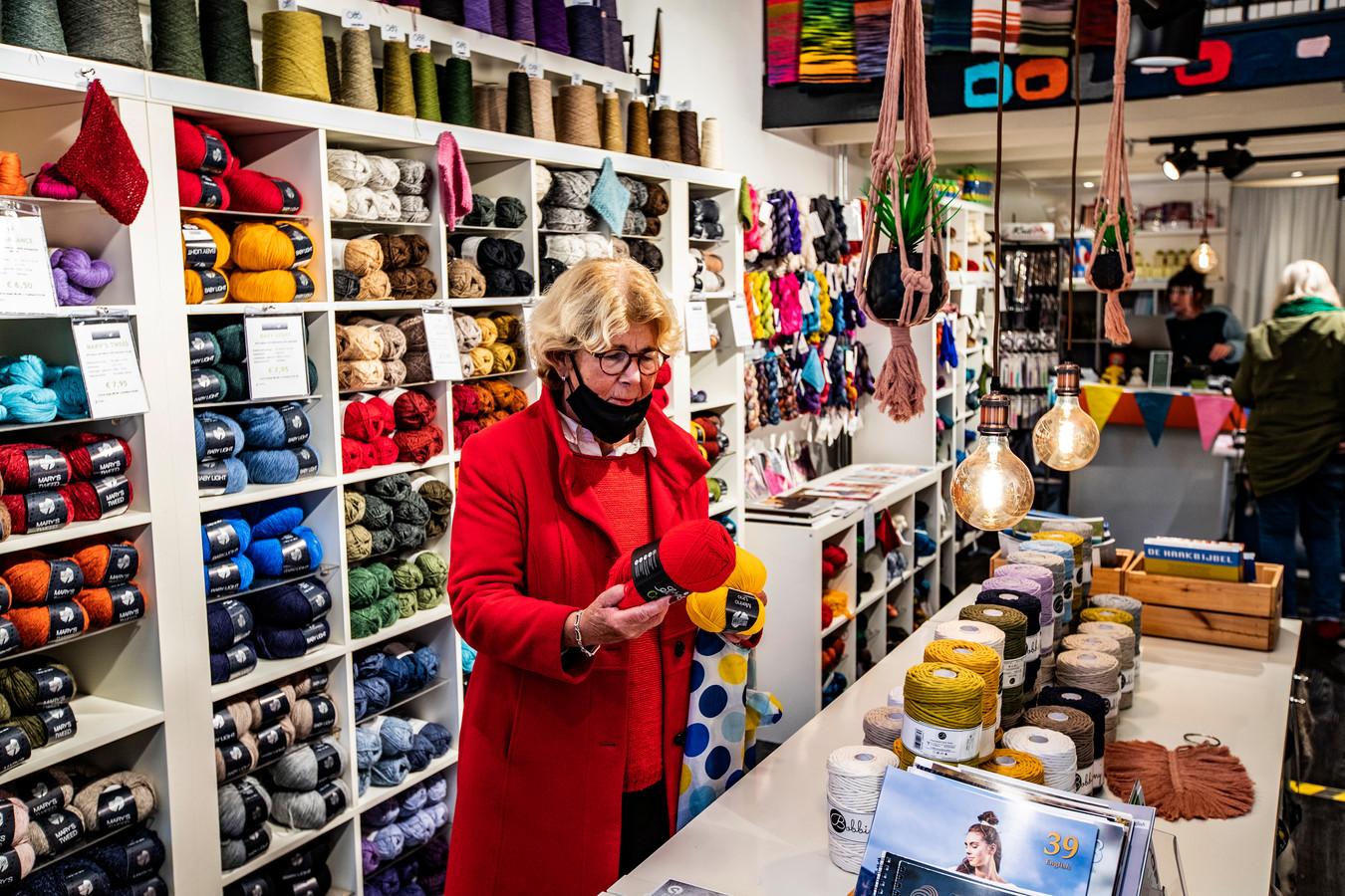 Tineke van Wezenbeek zoekt in Dol op Wol rode en gele knotten wol voor een Go Ahead-Eagles-sjaal.