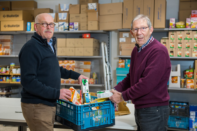 Coördinator Geurt Leppink (rechts) en Gerrit Poortman, verantwoordelijk voor de uitgifte, stellen een boodschappenpakket voor een cliënt samen.
