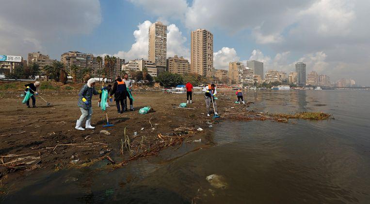 Vrijwilligers rapen rotzooi aan de oever van de Nijl, georganiseerd door het ministerie van milieu, VeryNile en Greenish. Beeld Reuters