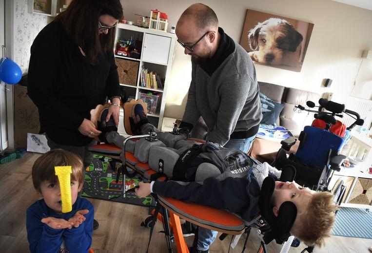 Geuko van Lang heeft een zeer zeldzame polio-achtige ziekte. Op de foto wordt hij op de staantafel gelegd door zijn ouders.  Beeld Marcel van den Bergh