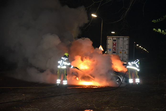 De brandweer blust de felle autobrand.