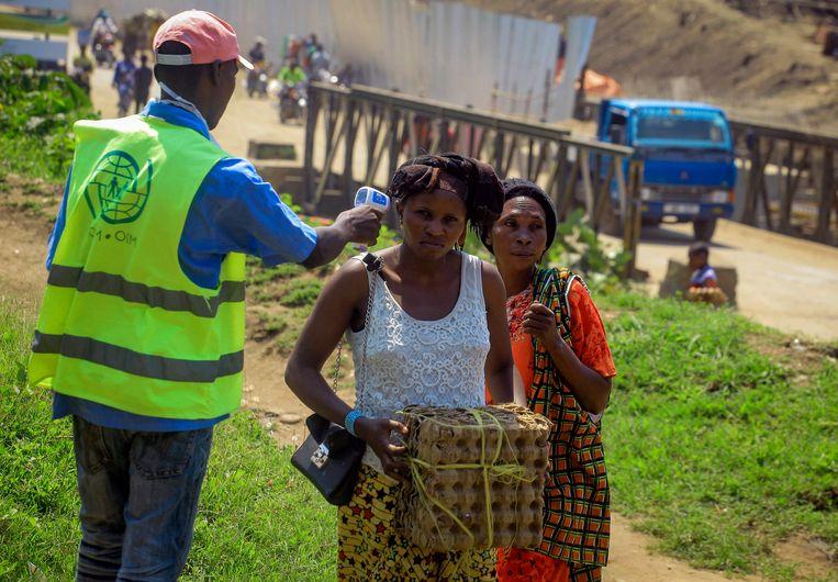 Een controleur aan de grens tussen Congo en Oeganda meet de temperatuur van een vrouw.  Beeld AP