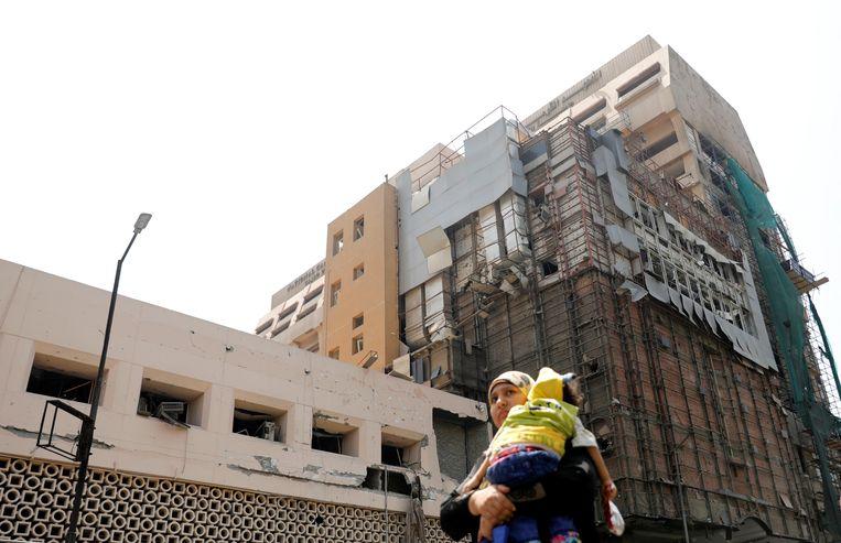 Een Egyptische vrouw draagt haar dochter, terwijl ze langs de beschadigde façade van een oncologisch centrum. Het gebouw werd zondag 4 augustus beschadigd door een brand als gevolg van een ontploffing.