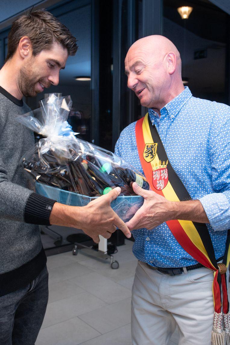 Thomas kreegt van burgemeester Denis Dierick een mand met streekbieren...