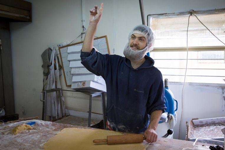 Ayal runt samen met zijn broer een bakkerij in Beit El. Hij wijst naar God, hij weet alles. Beeld Cigdem Yuksel