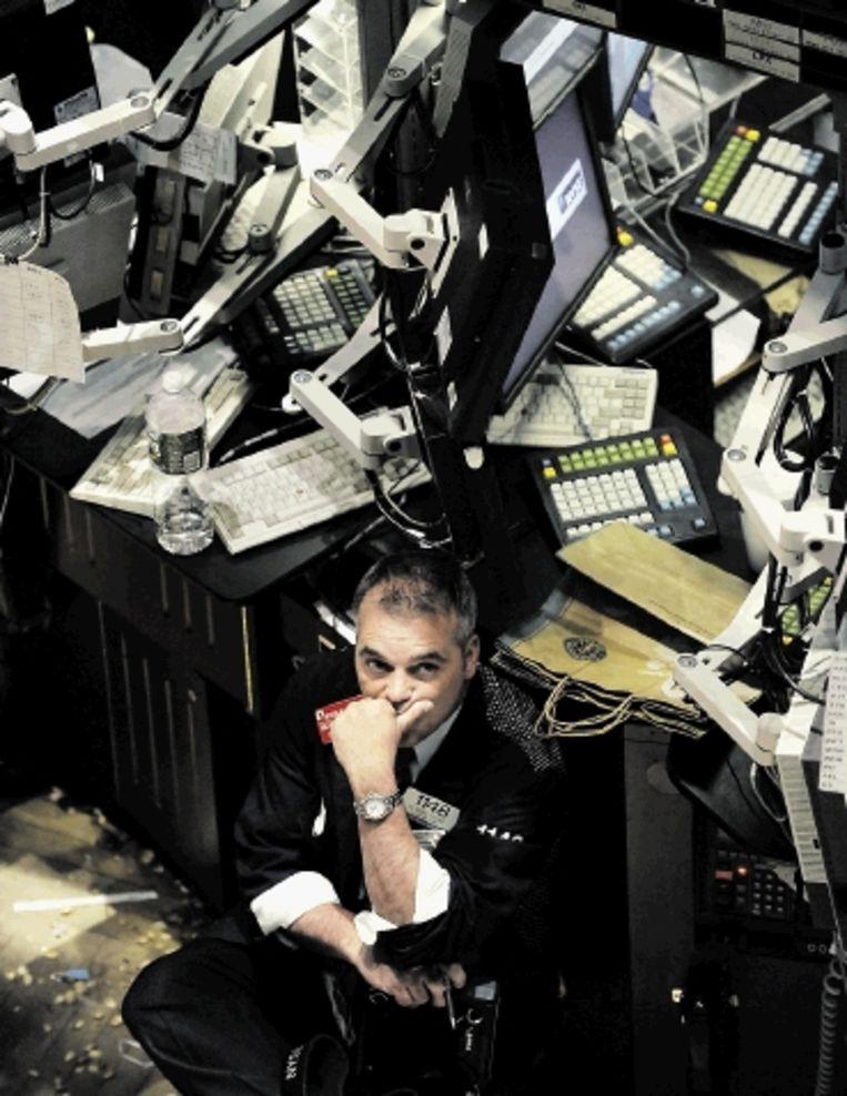 Een New Yorkse handelaar kijkt moedeloos naar de beurscijfers. ( FOTO AFP) Beeld AFP