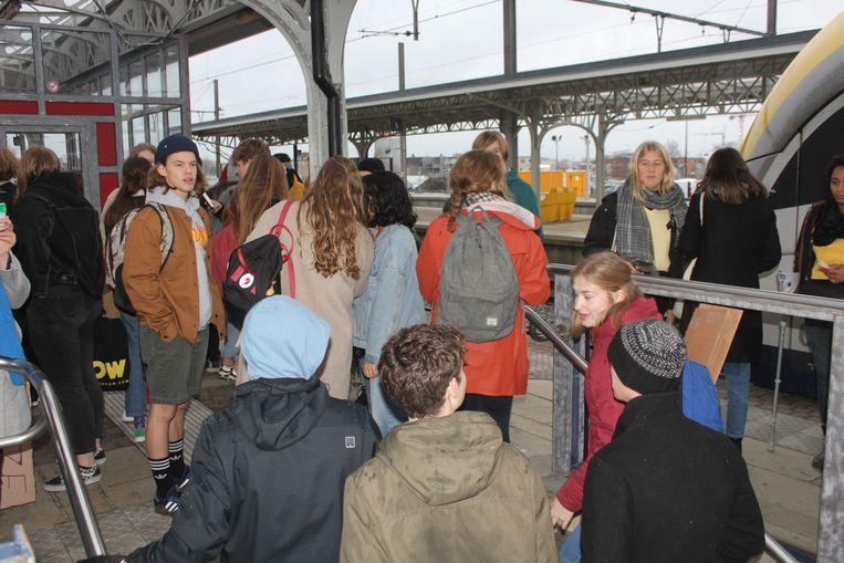 Het perron vol jongeren die wachten op de trein naar Brussel.