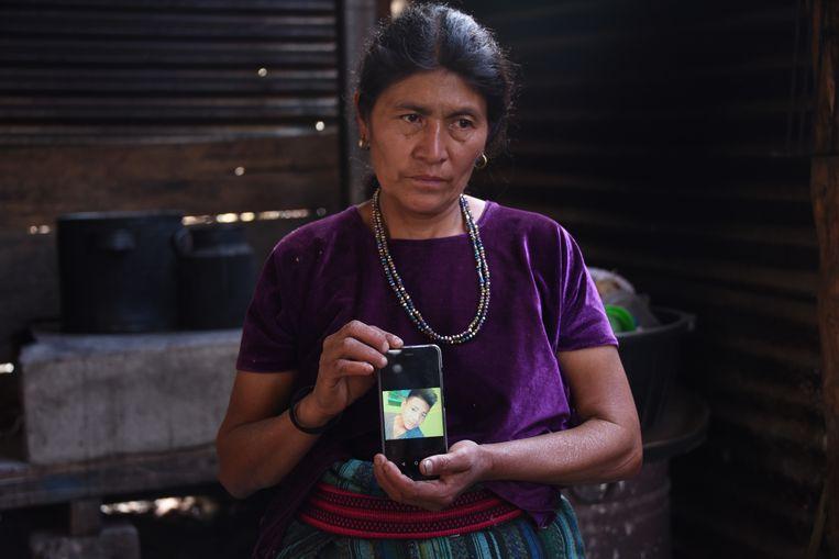 Rigoberta Vasquez, de moeder van de 16-jarige Carlos Gregorio Hernandez Vasque toont een foto van haar zoon. Beeld JOHAN ORDONEZ / AFP