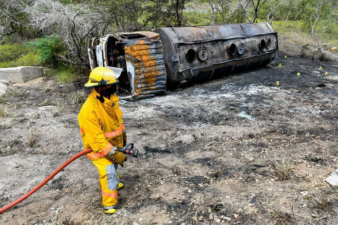Een brandweerman bij de resten van de verkoolde tankwagen.