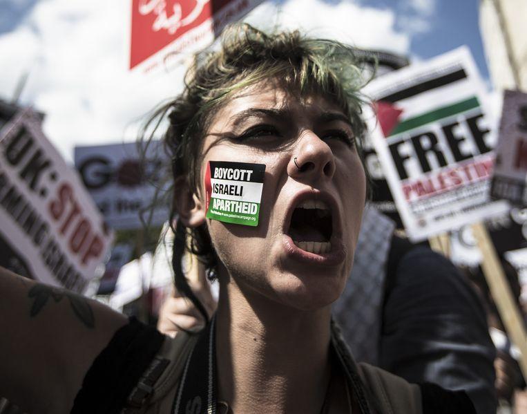 Actievoerders uiten begin augustus in Londen hun onvrede over het Israëlische offensief in Gaza. Op de wang van de demonstrant een sticker met de oproep tot een boycot van Israël, met een verwijzing naar de Zuid-Afrikaanse anti-apartheidsboycot van de jaren tachtig en negentig. Beeld Mark Esper / HH