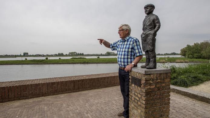 Jos Bakker bij het beeld De Zalmvisser op de Rijkswal in Woudrichem.