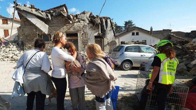 Vrouwen zoeken steun bij elkaar in het dorp Illica, nabij Accumoli. Beeld afp