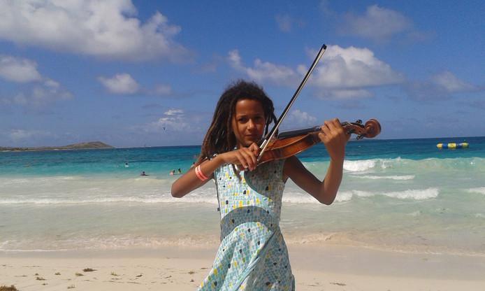 Tefari speelt viool. Hier op het strand van Sint Maarten.