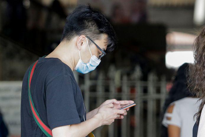 Een Chinese toerist draagt een mondkapje