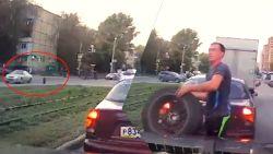 Wat een reflexen! Man springt uit zijn wagen om autoband tegen te houden