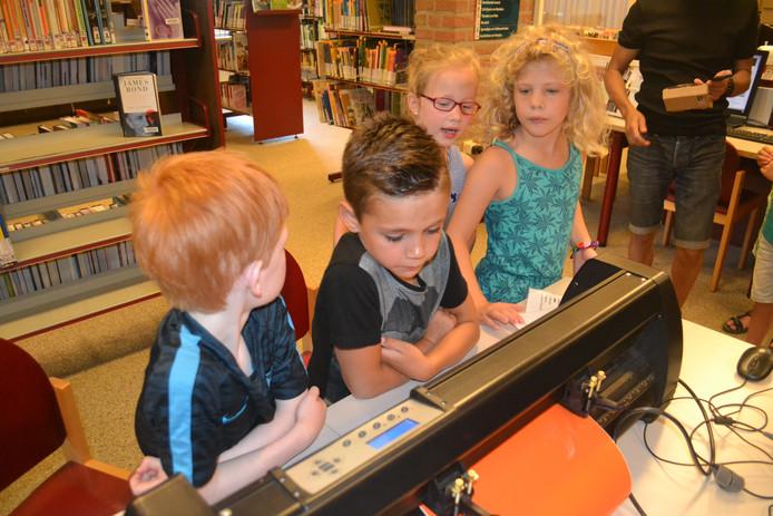 Kinderen wachten in spanning op het resultaat van de vinylplotter.