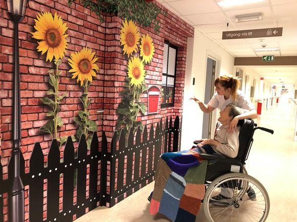 Ergotherapeute Laure De Troyer bewondert met bewoonster Liliane Lesy de zonnebloemen die een deur camoufleren.