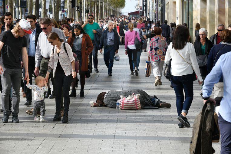 Weinigen kijken ervan op als op de Champs-Élysées in Parijs iemand ligt te bedelen.  Beeld Hollandse Hoogte / Peter Hilz