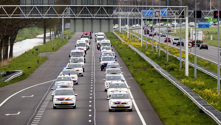 Een stoet politieauto's rijdt op de A7 met een gangetje van 60 kilometer per uur. Beeld anp