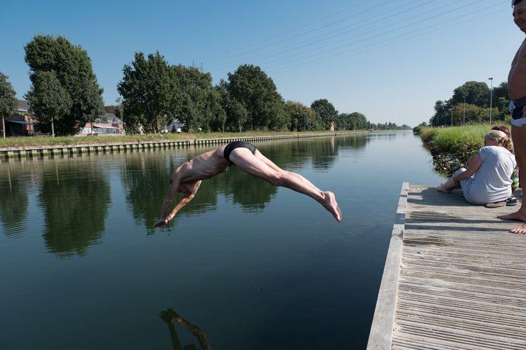 Een man neemt een duik in de Leuvense Vaart